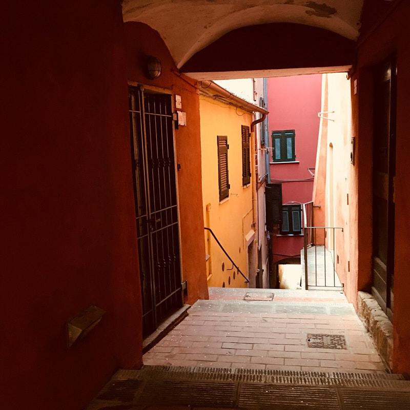 Volto con accesso a Via Roma, Lerici in stile ligure con facciate dalle tonalità calde, stretto carrugio e pavimentazione in mattoni rossi.