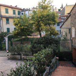 scalinata con vista su corte interna tra palazzi dai tipici colori liguri, verso Via Roma in centro a Lerici, Liguria. Case e volti in pietra con alberi in fiore.