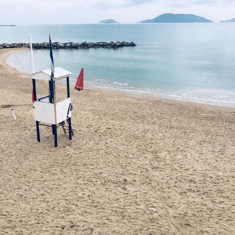 Lerici, spiaggia Venere Azzurra. Torretta bagnino bianca con bandiera Mare Blu ed ombrellone rosso. All'orizzonte isole Tino, Palmaria e scorcio di Portovenere.