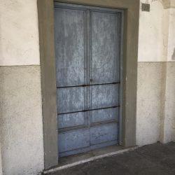 Via del Torrione Genovese Sarzana portone antico color celeste con barre di ferro orizzontali sotto un portico