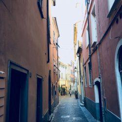 Via Rossi, Sarzana nel punto più stretto tra i palazzi color rosa e ocra con sanpietrini. Location Scout duzimage