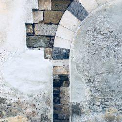Sarzana, sezione di muro nel centro storico di Sarzana. Pietra incastonata nell'intonaco formante un arco. location scout italia - duzimage