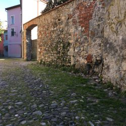 Via del Torrione Genovese Sarzana con pavimentazione antica in pietra, muri decadenti con pietra e mattoni a vista. Visuale in direzione nord. Location Scout duzimage