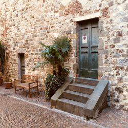 facciata sud Pieve di Sant'Andrea con gradini, portone verde, panchina in legno, piante, sampietrini e facciata in misto pietra e mattoni rossi. Location scout duzimage