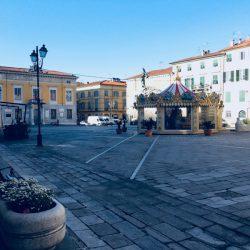 giostra in piazza Matteotti a Sarzana con pavimentazione lastricata e palazzo comunale sullo sfondo. location scout duzimage