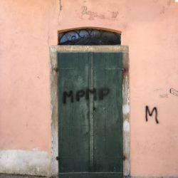 Via Torrione Genovese, Sarzana. Portone verde con graffity. Facciata rosa. Pavimento lastricato. Location Scout - duzimage