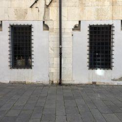 Piazza Matteotti Sarzana. Facciata con grandi finestre con inferiate. Cornice in marmo bianco e muro in pietra.