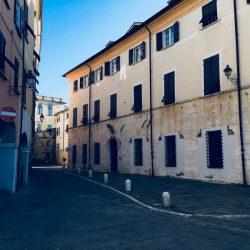 Piazza Matteotti Sarzana con facciate di palazzi storici e portici sul lato sinistro. Inferiate e portoni. Location Scout duzimage
