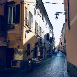 Via Mascardi a Sarzana con pavimentazione in sanpietrini, ristorante sulla sinistra con botte in legno e tavolini. Vista direzione sud. Location scout