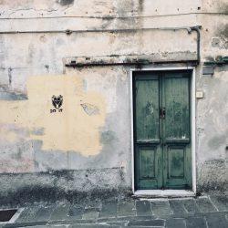 Sarzana, muro in stato decadente con portone in legno verde, accenni di pittura gialla e stencil. Parete nei pressi di Piazza Matteotti fotografata per location scouting italia - duzimage