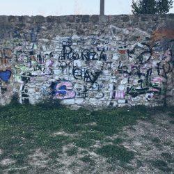 muro sotto la circonvallazione di Sarzana. Pietra e graffity con suolo in erba e terra. Location scout duzimage