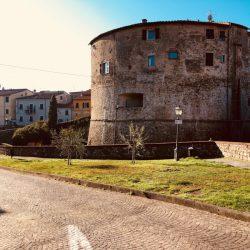 Torrione Sarzana in mattoni. Architettura storica fronte giardini e zona pedonale. Sampietrini. Location Scout duzimage