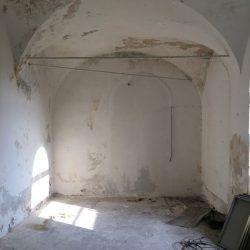 interno di luogo abbandonato con architettura a volte e spazzatura a terra. Muri intnacati di bianco scristati. Calcinacci. Location Scout duzimage