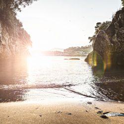 spiaggia privata tra la Caletta ed Eco del Mare vista al tramonto con riflesso del sole, scogli e gabbiani in volo. Location Scout Italia - duzimage