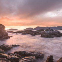 tramonto sul Golfo dei Poeti visto dagli scogli tra le due spiagge di Fiascherino. Scogli in primo piano ed acqua del mare tinta di viola. Cielo nuvoloso. Location scout italia - duzimage
