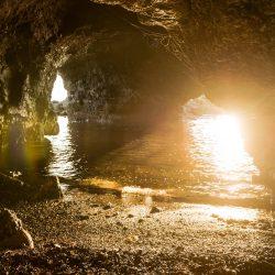 Grotta nei pressi di Fiascherino ed Eco del Mare fotografata da una piccola spiaggia dentro alla grotta con acqua limpida e scogli illuminati dalla luce del tramonto - Locartion Scout Italia - duzimage