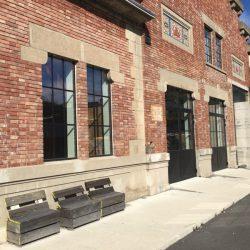 Facciata ristrutturata di una sezione delle Ex Ceramiche Vaccari con mattoni rossi, grandi finestre e panchine in legno. Location scout duzimage https://www.duzimage.com/category/locationscouting/