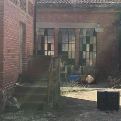 Facciata dismessa in evidente stato d'abbandono con vetrate rotte, mattorni rossi e vegetazione. Location scout duzimage https://www.duzimage.com/category/locationscouting/