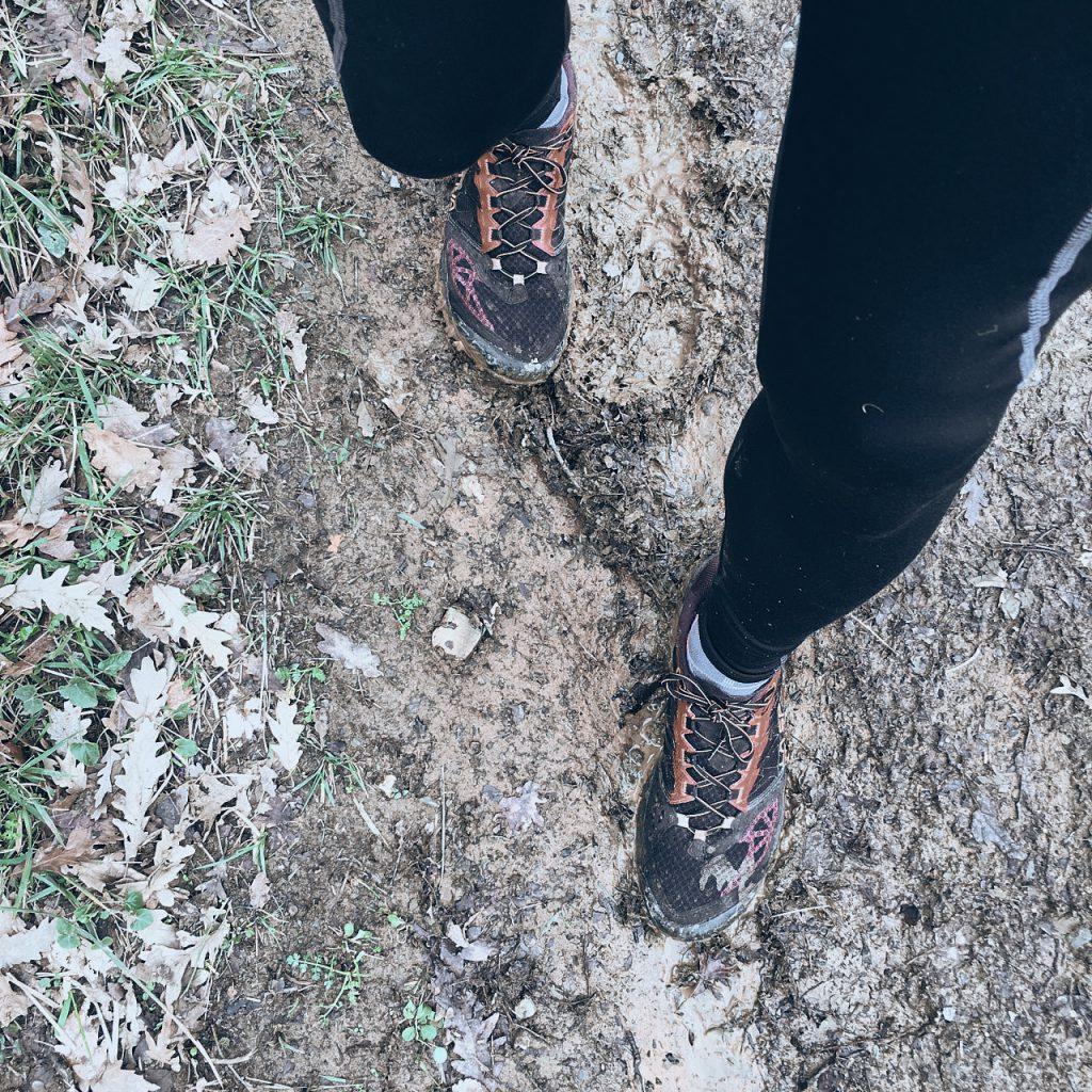 ripresa dall'alto verso il basso di un paio di piedi con scarpe da running nel fango